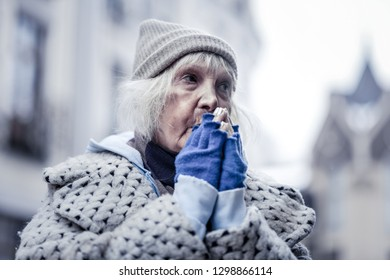 Cold winter. Unhappy poor woman feeling very cold while being outside in winter