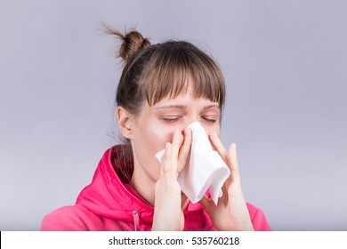 Cold woman holding handkerchief blowing nose