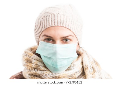Cold woman wearing surgical mask and knitted warm clothes isolated on white background