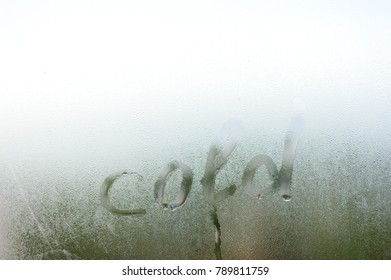 """Cold"" word written on fresh condensation on window glass fogged textured natural background"