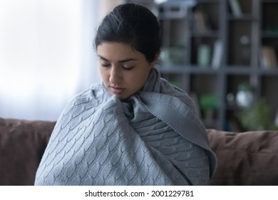 So cold. Young indian woman wrap up in blanket freeze at home feel ague shiver because climate control heating system is broken. Sick female teenager trying to warm up in cool living room under plaid