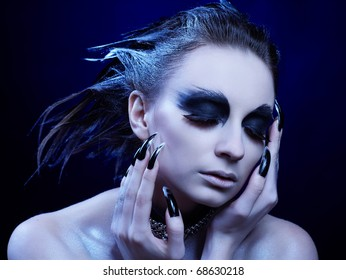 cold-tint portrait of beautiful girl with bird of prey make-up, hair-do and manicure