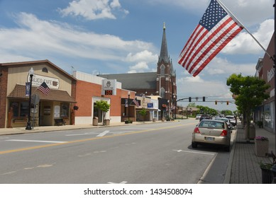 Coldwater, OH, May 25, 2019, small town American Heartland main street with cafe, bank, Catholic Church with tall steeple and an American Flag flying from a lamp post