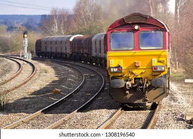 COLESHILL, WARWICKSHIRE, UK - MARCH 14, 2013: EWS-liveried DB Schenker Class 66 No. 66129 rounds the curve at Coleshill Parkway, hauling a train of empty steel carriers on the 6V92 Corby to Margam.