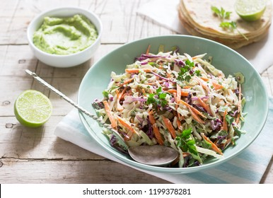 Coleslaw made from cabbage, carrots and various herbs, served with tortillas and guacamala on a wooden background.
