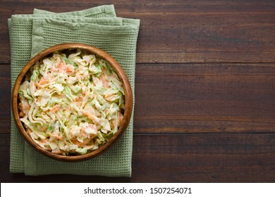 Coleslaw made of freshly shredded white cabbage and grated carrot with homemade mayonnaise-based salad dressing, photographed overhead with copy space on the right side (Selective Focus on the salad)