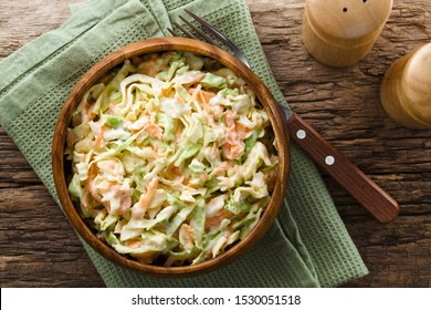 Coleslaw made of freshly shredded white cabbage and grated carrot with homemade mayonnaise-based salad dressing in wooden bowl, photographed overhead (Selective Focus, Focus on the salad)