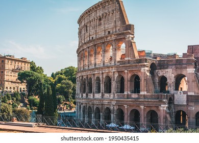 Coliseum (Colosseum), Rome, Italy. Ancient Roman Coliseum is famous landmark, top tourist attraction of Rome. Scenic view of Coliseum with trees and blue sky. Sunny old Coliseum close-up in summer.