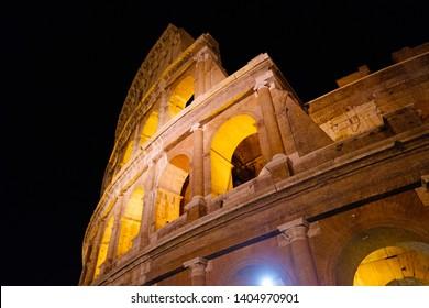 Coliseum Flavian amphitheater night view with colorful lights, Roma Italy. Anfiteatro Flavio Colosseo. Romantic Italian evening near Colosseum, famous tourist landmark. Antique roman gladiator arena.