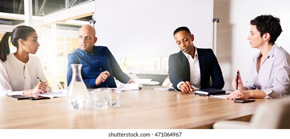 collaberation between 4 racially diverse eclectic business executives on their new small business venture together as partners, taking place at a modern office at the end of a large conference table.