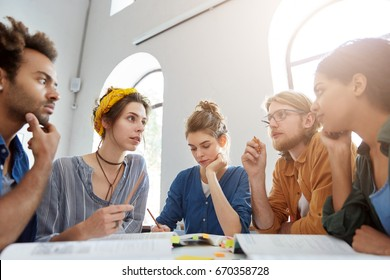 Collaboration and brainstroming concept. Portrait of interracial friends gathering together sitting at table in classroom surrounded with books having debates expressing their opinions and views.