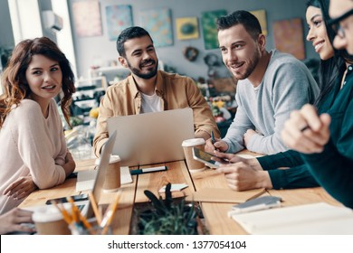 Collaboration. Group of young modern people in smart casual wear discussing something and smiling while working in the creative office