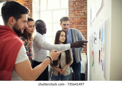 Collaboration is a key to best results. Group of young modern people in smart casual wear planning business strategy while young man pointing at infographic displayed on the white wall in the office