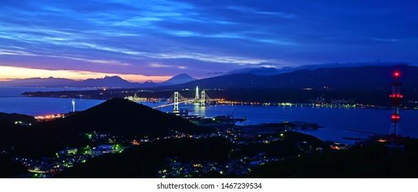 Collaboration scene of Hakucho Ohashi and the Mt. Yotei dyed at sunset seen over Muroran Port at Hokkaido