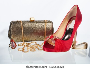 Collage of accessories on glass table with red high heel shoes, gold bracelet, precious stone ring and gold clutch purse