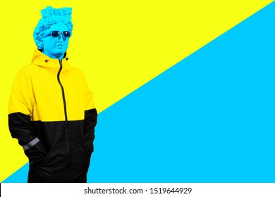 Collage of contemporary art. Concept. Gypsum head of Apollo's in sunglasses. A man in a jacket. On a yellow and blue background.