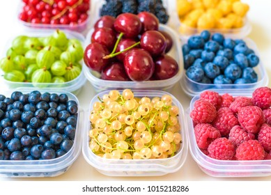 Collage of different fruits and berries isolated on white. Blueberries, cherries, blackberries, grapes, strawberries, currants. Collection of fruits and berries in a bowl. Top view.