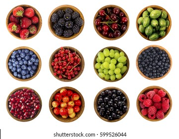 Collage of different fruits and berries isolated on white. Blueberries, cherries, blackberries, grapes, strawberries, currants and pomegranate. Collection of fruits and berries in a bowl. Top view.