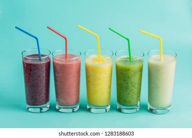 collage of exotic blended juice in glasses with straws on the isolated blue background. different vitamins for health . treatment