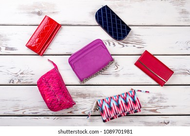 Collage from female bags and purses. Makeup bags on white wooden background. Set of women fashion wallets.