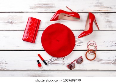 Collage of female red fashion accessories. Stylized flat lay of ladies red beret, heels, purse and accessories, top view. Set of women fashion outfit and beauty essentials.