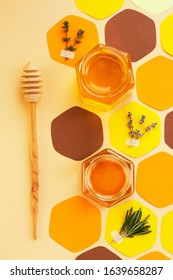 Collage - a jar of honey in the shape of a hexagon and a honeycomb, cut out of colored paper, with melliferous herbs and a spoon for honey. Vertical format, social-media-ready.