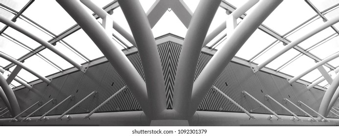Collage photo of glass and metal structures resembling futuristic building. Abstract black and white modern architecture or construction industry panoramic photo with multiple steel pillars / girders.