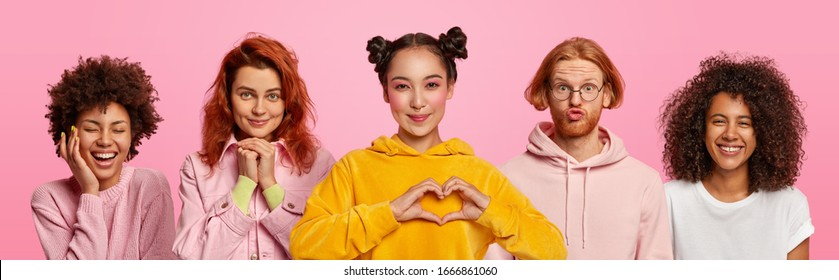 Collage shot of mixed race four diverse women and one man express positive emotions, smile pleasantly, Asian female shapes heart gesture, stand next to each other, isolated on pink background
