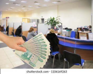Collage with visitors in bank and hand with money, thousand ruble notes