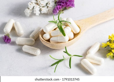 Collagen capsules for skin and beauty in the wooden spoon with herbs and flowers on white marble table close up. Health care concept.