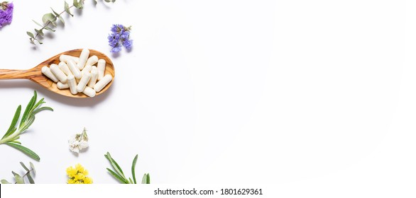 Collagen capsules for skin care and beauty in the wooden spoon on white background with herbs and flowers. Health care concept. Long banner format.
