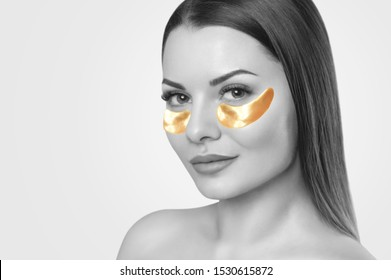 Collagen gold patches on the skin of the eyelid, on the face of a beautiful woman. Cosmetology concept. The photo is black and white.