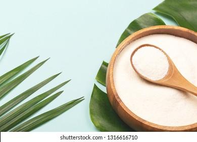 手のひらの葉の背景に鉢にコラーゲン粉と計測スプーン。余分なタンパク質の摂取。自然の美しさと健康の補足。最小限のコンセプト。植物を基にしたコラーゲン。平面、上面図。スペースをコピーします。