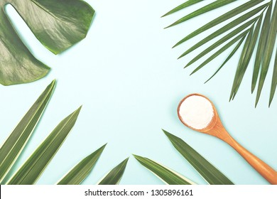 Collagen powder in measure spoon on palm leaves background. Extra protein intake. Natural beauty and health supplement for skin, bones. Plant based collagen concept. Flat lay, top view. Copy space.