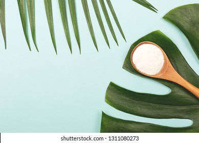 Collagen powder in measure spoon on palm leaves background. Extra protein intake. Natural beauty and health supplement for skin, bones. Plant based collagen concept. Flatlay, top view. Copy space.