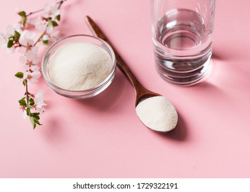 Collagen powder in wooden spoon, supplement with galss of water and flowers, healthy and anti age concept  on pink background, top view, copy space