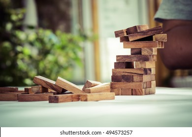Collapse motion of wood blocks stack game after a man's hand played