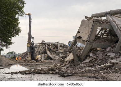 Collapsed industrial buildings with a huge machine driller and workers in orange reflective suits.