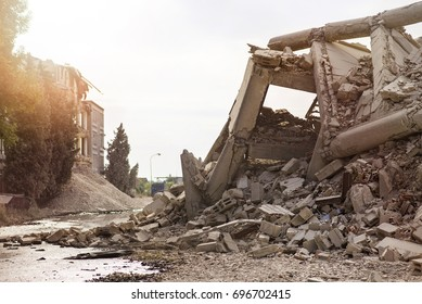 Collapsed industrial concrete building with plenty of dust and debris, broken columns and water leaks with haze sun.