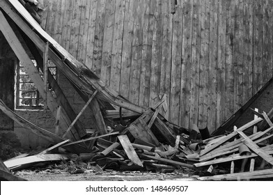 Collapsed roof wooden wall and broken window in abandoned house interior.