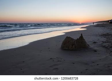Collapsed sand castle atMatalacanas beach during the magnificent sunrise. Costa de la Luz, Spain