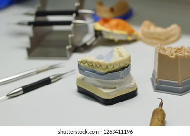 collapsible dental model with metal-ceramic and metal-free crowns, wax modeling of teeth, on a black background, dental instruments, wax for modeling teeth, electroplating