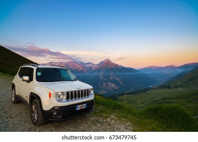 Colle delle Finestre, Italy - June 22, 2017: White Jeep Renegade parked on dirt road at panoramic view point on the Italian Alps from above. Colorful sky at sunset, mist on the valley below.