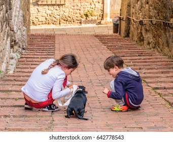 COLLE VAL D'ELSA, ITALY - APRIL 25, 2017 - Two kids play with a puppy dog in an alley of Colle Val d'Elsa.