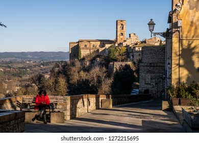 COLLE VALDELSA, ITALY - DECEMBER 26, 2018: Unknown woman, the towers of the church of Santa Caterina and the Praetorian Palace of the medieval village of Colle Valdelsa, Siena, Tuscany