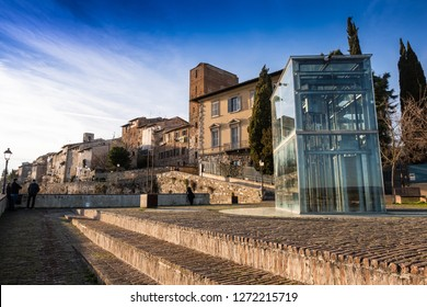 COLLE VALDELSA, ITALY - DECEMBER 26, 2018: Two unknown people. The Baluardi with its crystal lift offer a panoramic view of the city in the historic center of Colle Valdelsa, Siena