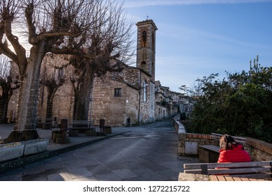 COLLE VALDELSA, ITALY - DECEMBER 26, 2018: Unknown woman near the church of Santa Caterina in the medieval village of Colle Valdelsa, Siena, Tuscany