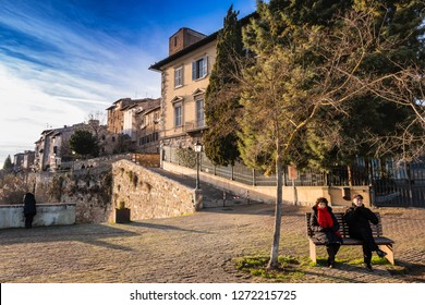 COLLE VALDELSA, ITALY - DECEMBER 26, 2018: Two unknown people in the Baluardi. Panoramic view of the city in the historic center of Colle Valdelsa, Siena