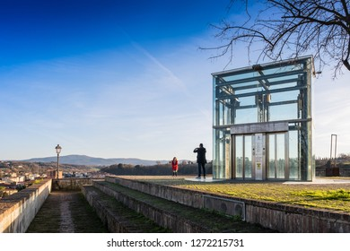 COLLE VALDELSA, ITALY - DECEMBER 26, 2018: Two unknown people in the Baluardi with its crystal lift offer a panoramic view of the city in the historic center of Colle Valdelsa, Siena