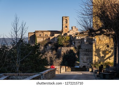 COLLE VVALDELSA, ITALY - DECEMBER 26, 2018: Unknown woman, the towers of the church of Santa Caterina and the Praetorian Palace of the medieval village of Colle Valdelsa, Siena, Tuscany